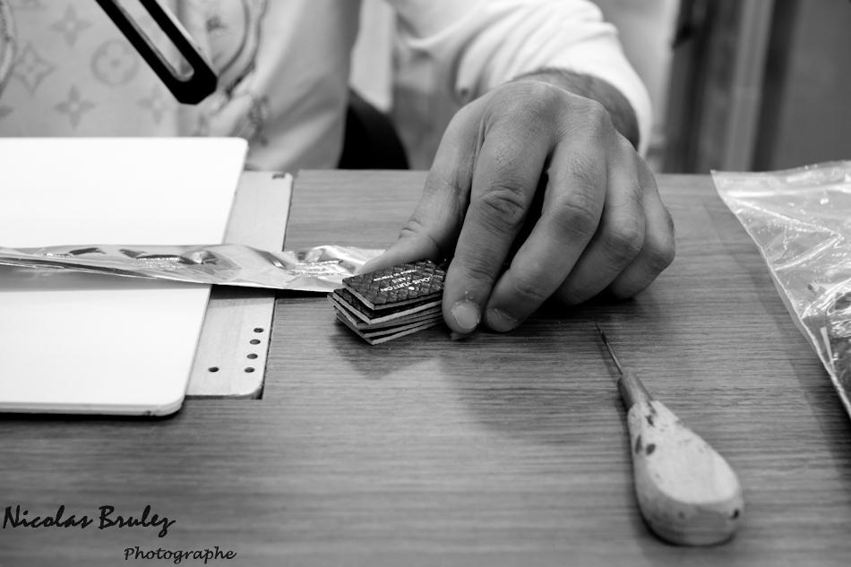 photos exlusives des artisans des ateliers louis vuitton à asnières sur seine pendant les journées particulières. Ici un artisan appose un marquage à l'or sur le cuir